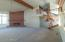 Vaulted ceiling with beam, brick fireplace & red oak stairway leading to loft