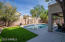 Resort-like backyard with pool, artificial turf and covered patio.