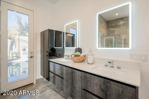 Stunning bathroom with gorgeous cabinetry and lighted mirrors