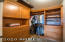 Walk in closet for guests is richly appointed with custom cabinets.