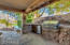 Covered patio off kitchen with built-in stone bbq with grill and bar area.