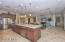 Granite slab counters, designer cabinetry, and stainless appliances, including a wall oven and gas cooktop