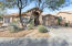Front view of home with mature desert landscaping and two car garage.
