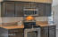 Dark wood cabinets with quartz countertops and stainless steel appliances.