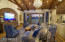 T&G entertainment wall, with solid wood trusses, with a grand chandelier, and custom cabinetry.