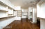 MASSIVE Owner's Suite closet with hand scraped wood flooring, natural light, & a variety of storage options