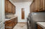 10' x 9' Laundry w/Nutone wall iron board, loads of cabinetry, & SS sink w/pullout sprayer