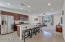 Kitchen features stainless steel appliances, kitchen island, granite countertops, cabinet hardware and tile flooring.