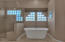 Beautiful stand alone tub and large tiled shower.