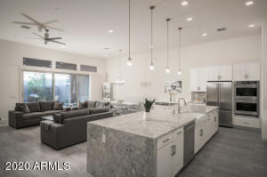 Sleek flat white panel cabinetry, waterfall island, granite countertops and matching granite backsplash up to cabinets and brushed nickel hardware give this home a 2021 vibe.