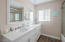 The guest bathroom features double sinks, and the same quartz counters, and beautiful white cabinets as seen in the kitchen