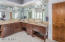 Dual sink Master bath with large walk-in closet and travertine countertops