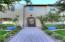 Professionally landscaped yard with synthetic turf in front. Planters provide pops of color.