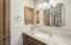 The guest house bathroom offers a walk-in shower and single vanity.