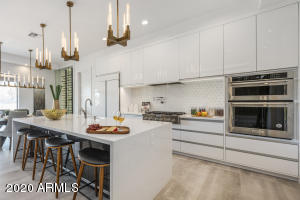 The gourmet kitchen is upgraded with European style cabinetry, KitchenAid appliances, custom lighting, and backsplash.