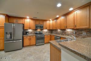 Kitchen has granite countertops, breakfast bar, wood cabinetry, and GE slate-finish appliances, including gas range