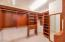 The owner's closet is finished with custom built-in cabinetry.
