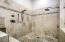 Enjoy the walk-in shower with dual shower heads, stone flooring, and marble surrounds with glass enclosure.