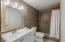 Updated secondary bath with ceramic tile flooring, updated single cultured marble sink with vanity, updated ceramic tile shower and ceramic tile wainscot