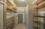 Large master walk in closet with custom shelving details.