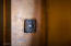 Hammered copper boarders the front door and provides the perfect rustic backdrop for this home's doorbell.