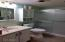 Bathroom features, hi rise toilet, glass shower doors, heat lamp, emergency pull cord and linen closet