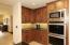 Double ovens with built in microwave surrounded by warm, rich cabintry