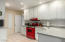 Kitchen with subway tile and retro-red gas stove.