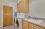 The laundry room features a sink and cabinets along with a door to the single garage.