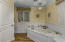You have a private water closet and an amazing jetted soaking tub surrounded by marble and adorned with a gorgeous chandelier above.