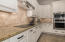 Recently updated kitchen with white, granite, neutral tile and stainless steel appliances