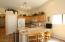 Kitchen has large bar seating area and maple cabinets.