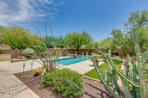 Coveted LOT SPACE! Nearly twice the size as average lots offered in this community. Incredible pool, year round green turf, immaculate designer pool with water feature, built in BBQ, Shaded patio seating!