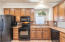 """Kitchen offers RO at sink and refrigerator, 42"""" upper cabinets, pantry cabinets, Corian countertops, built in appliances."""