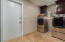 Large laundry area, cabinets, built-in ironing board and window for natural lighting