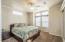 Spacious bedroom with bay window, ceiling fan with light, custom Iron window valance.