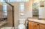Bathroom offers a Tiled shower with built in corner shelf, double glass slider door,