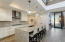 Custom lighting, huge waterfall island with rich granite counters, gleaming stainless steel appliances