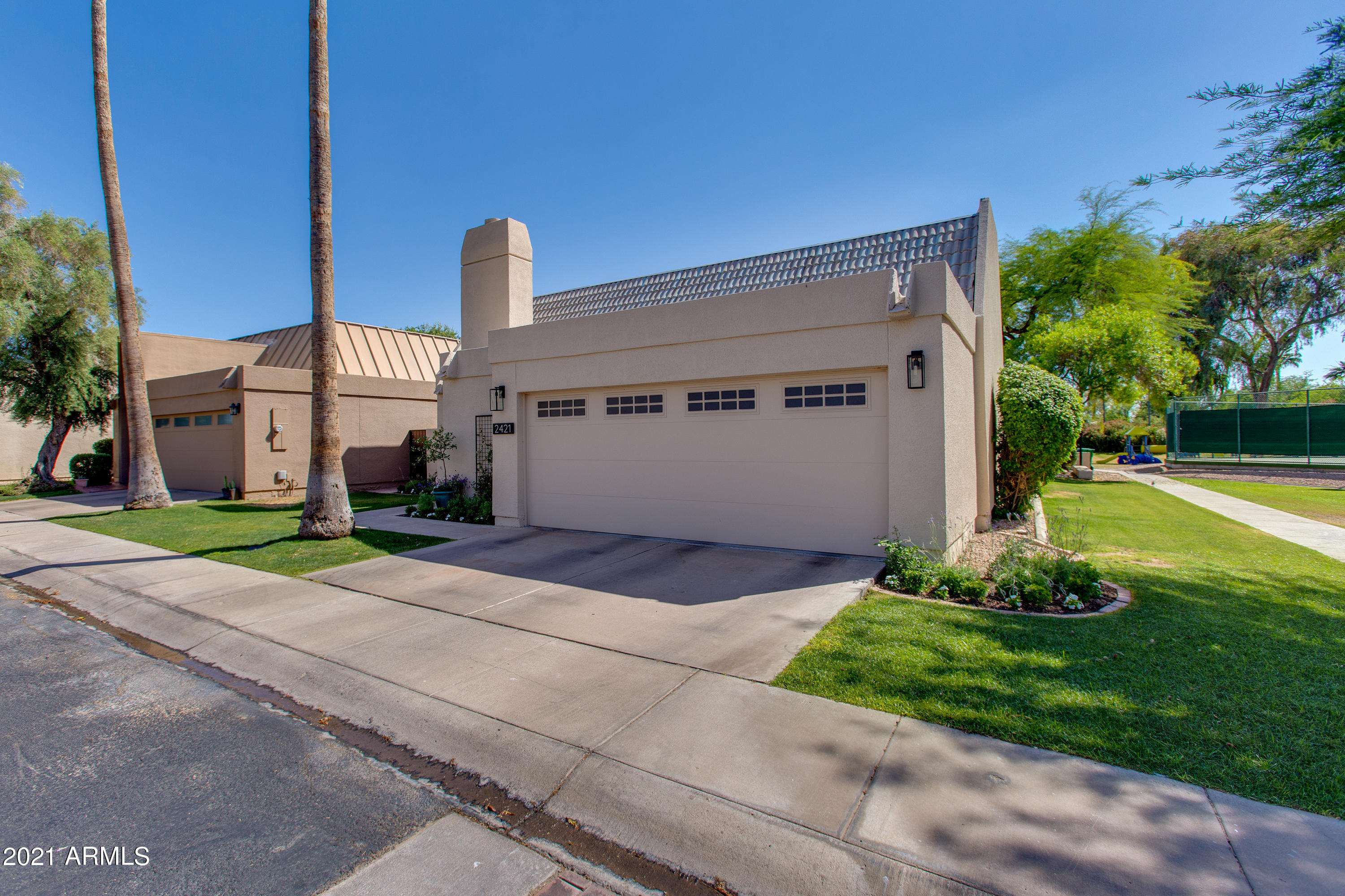 This one checks all of the boxes! Enjoy the privacy of a guard-gated Biltmore community, the modern feel of the clean finishes and open interior concept, the convenience of a low maintenance yard, and the storage offered by a two-car garage. The entire home has been tastefully upgraded and features high ceilings, beautiful tile, quartz countertops, subway tile backsplashes, and contemporary fixtures. The backyard is designed with lush green grass and a spacious wood-beamed patio. Adjacent to the community tennis courts, this end unit feels more like a corner lot on a quiet street.