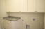 Laundry Room complete with cabinets and granite countertops.