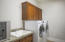 Equipped with a laundry room sink and some cabinetry.