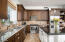 Stainless steel appliances with built-in refrigerator. Dual tone granite counter tops.