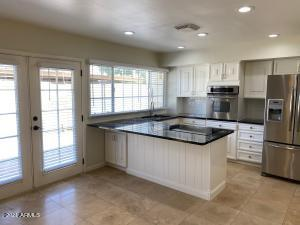 modern open concept kitchen with French doors out to large patio
