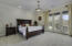 Master Bedroom with Double French Doors that open out onto outdoor Veranda into backyard just footsteps from pool