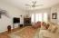 Great room features gas fireplace, plantation shutters, wood flooring & updated ceiling fan.