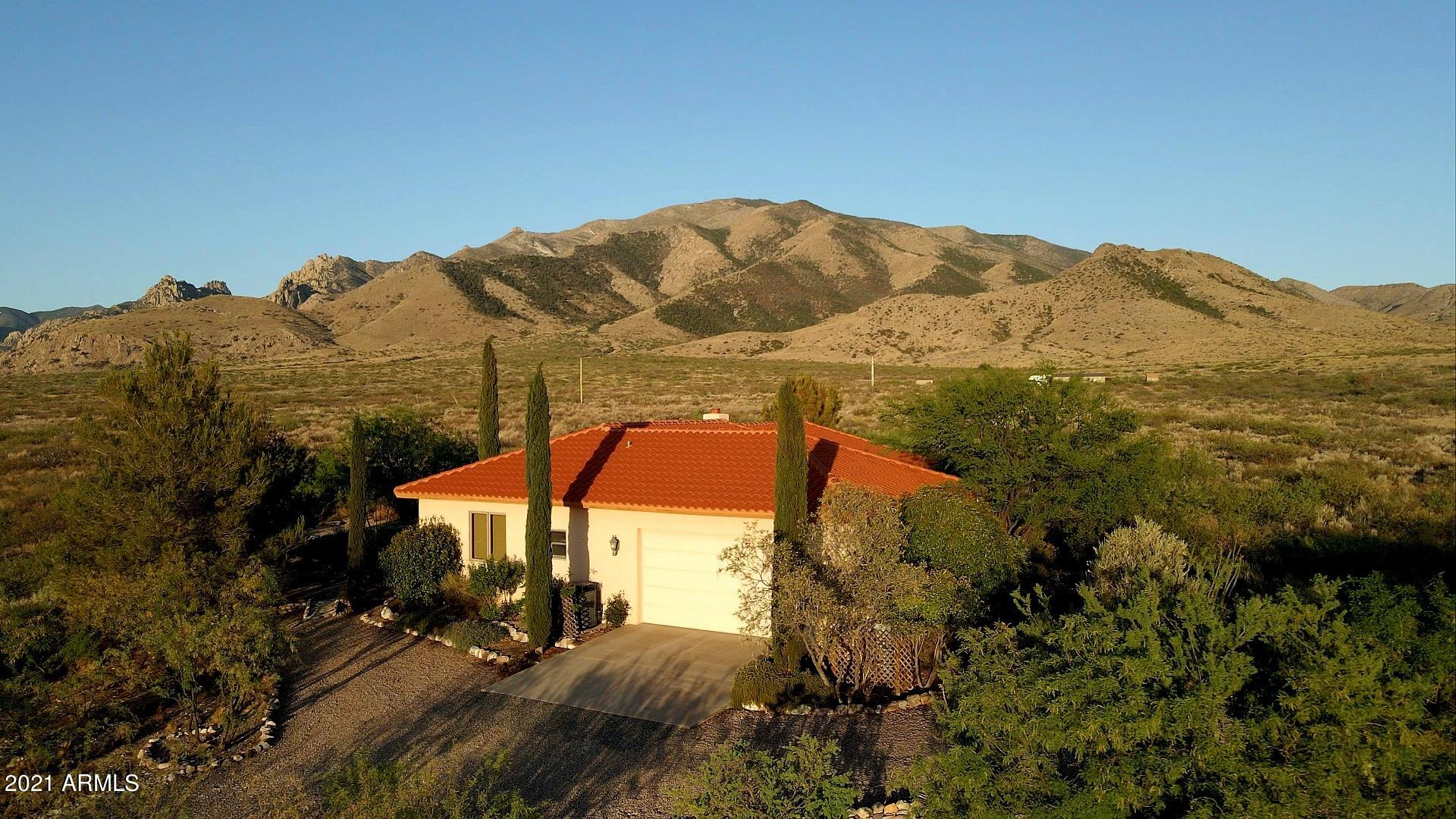 Peaceful custom home surrounded by mountain views and nature.  This tranquil three bedroom home includes a full bathroom in each bedroom, plus a hall bath, extra storage, fireplace, recessed lighting,  AC, entertainment room, solid wood cabinets, covered patio, tile roof, dual pane windows, scored concrete floors, 2 stall barn, 2 car garage, garden area and so much more all on 10 acres! Secluded without being isolated this home is both a retreat and perfect for entertaining. The unique custom-built home with two stall horse barn sits on a peaceful ten acres at the foot of the Dragoon Mountains. Watch unobstructed sunrises and marvel at the clear night sky. Enjoy 360 views, an abundance of wildlife, or a 10 minute walk into the National Forest for a great hike or leisurely horseback ride.