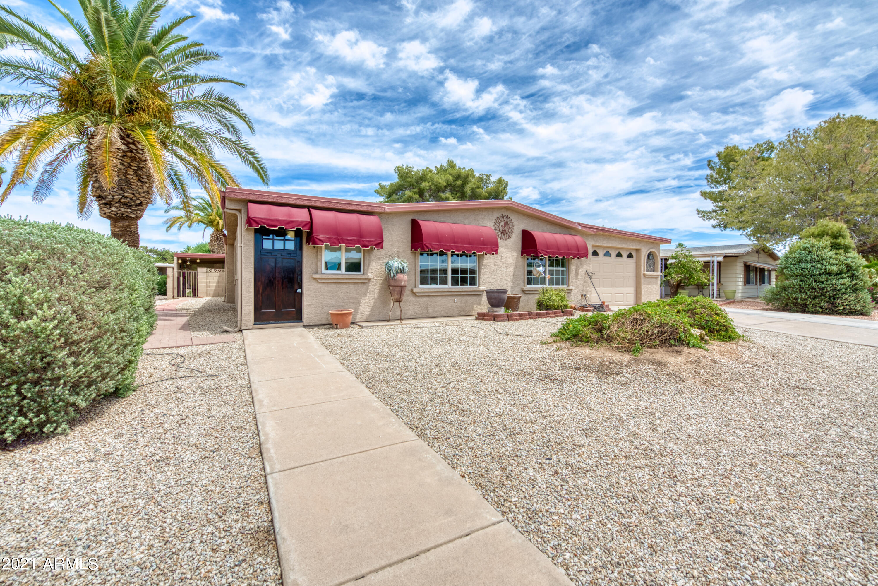 This 1,248sf 2BR/2BA affixed stuccoed mobile home provides a spacious floorplan complete with large kitchen + island/breakfast bar, dining + family room, oversized office/den/flex room, & inside laundry. No interior steps or carpet with only laminate + tile flooring throughout. Step outside to this fully fenced backyard oasis complete with large covered patio, pet-friendly artificial turf, and, yes ... a sparkling, private pool! Find two generously sized exterior storage spaces, enclosed carport with built-in shelving + garage door, all offering plenty of room inside & out. This sought-after active-adult subdivision offers its own clubhouse, lakes, golf, tennis, pickleball & fitness center. Close to nearby Sun Lakes amenities, shopping, restaurants and more!