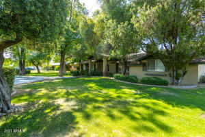Lushly landscaped lot with plenty of shade and grass.