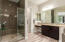 The walk-in shower is surrounded by custom tile.