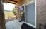 Covered patio leading from the home to the detached laundry room.